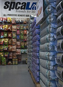Pallets with large stacks of dog food bags placed in aisle. Bags of pet treats and food hanging on wall under spcaLA banner