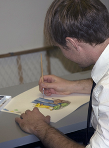 Side view of man painting cartoons on paper
