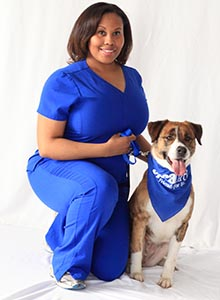 African American woman wearing blue scrubs kneeling next to brown and white shepherd mix dog wearing blue spcaLA bandana. White background