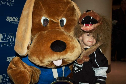 Dog mascot wearing blue shirt kneels next to young boy wearing a lion hat and wearing an LA Kings jersey in front of spcaLA backdrop