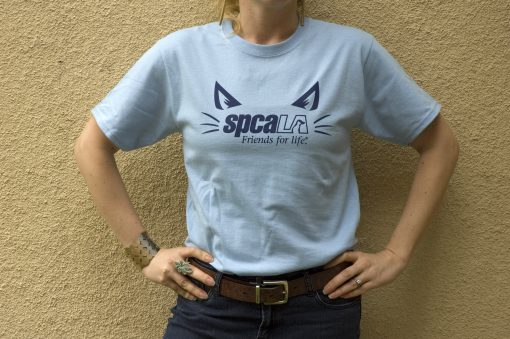 Woman wearing light blue tshirt with a dark blue spcaLA logo surrounded by cat ears and whiskers