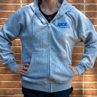 Woman wearing grey sweatshirt with blue spcaLA logo over left chest area