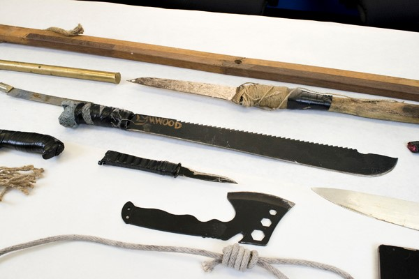 Several homemade bladed weapons laying on white table.